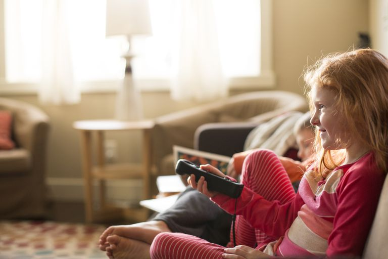 Young, happy girl watches tv. istockphoto. ADHD
