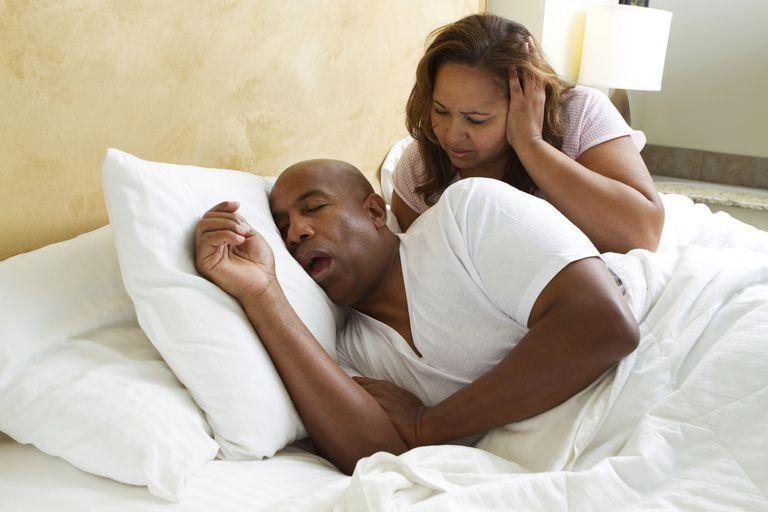 man snoring next to disgruntled wife
