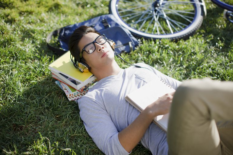 Student listening to headphones in grass
