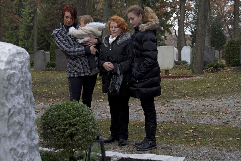 Multigenerational family visiting gravestone in cemetery