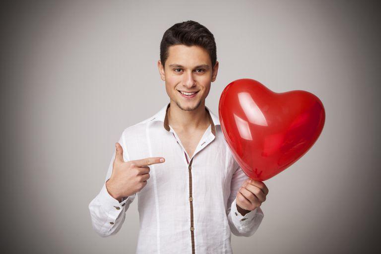 A man holds a heart shaped balloon.