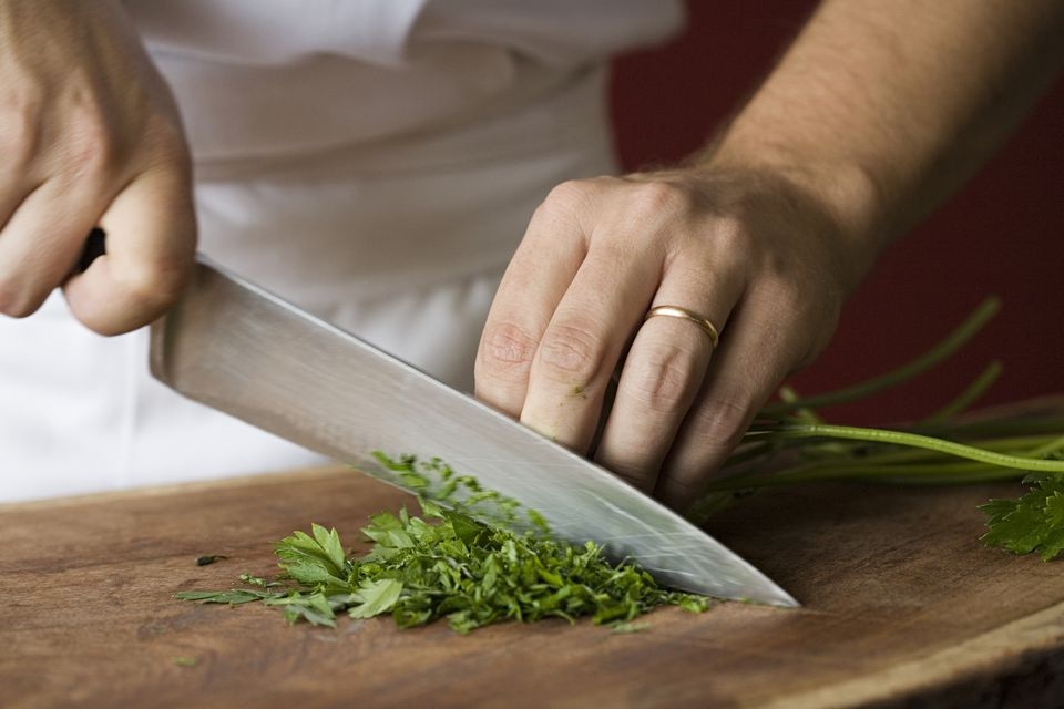 A chef chopping cilantro.