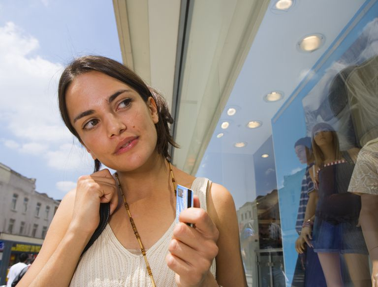 Young woman holding credit card, looking in shop window, outdoors