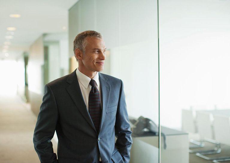 Businessman walking down modern office corridor