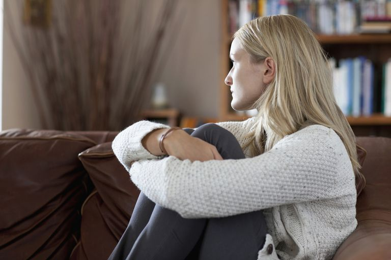 Anxious woman sitting in sofa daydreaming
