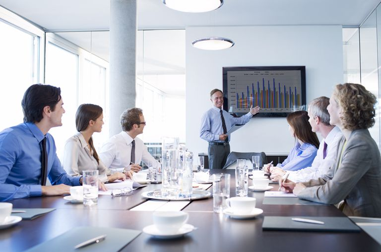 businessman giving presentation to table of executives