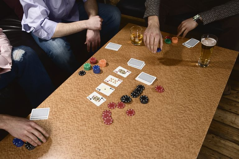 Three young men playing poker, one placing bet, close-up