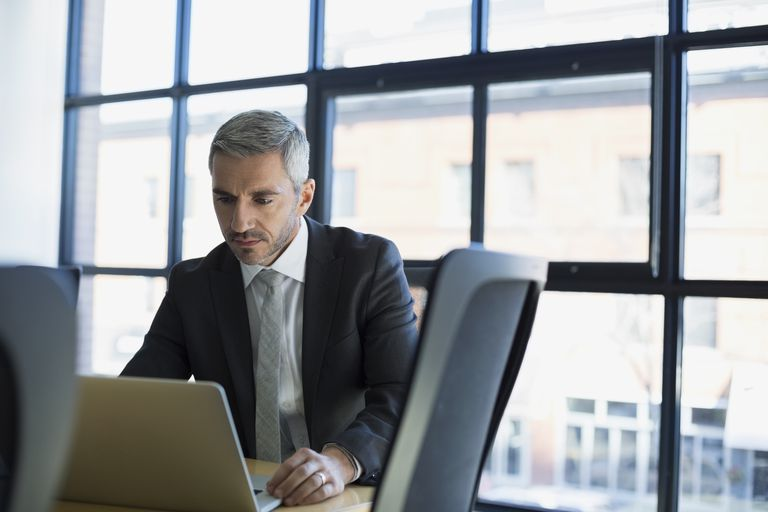 Focused businessman working at laptop in conference room