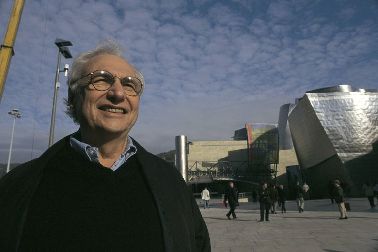 Frank Gehry stands smiling near his museum in Bilbao, Spain, the Guggenheim