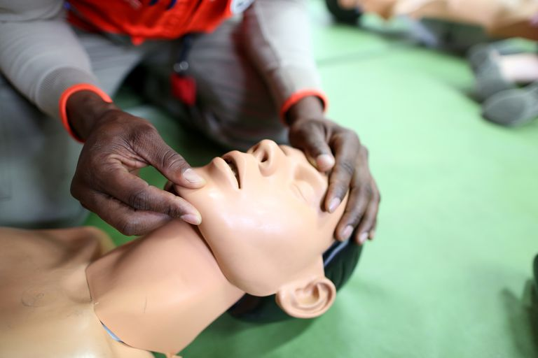 Man tilting the head of a cpr dummy back