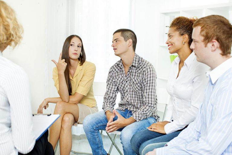 'Group Therapy, meeting of support group with their counselor. Selective focus to young woman talking.'
