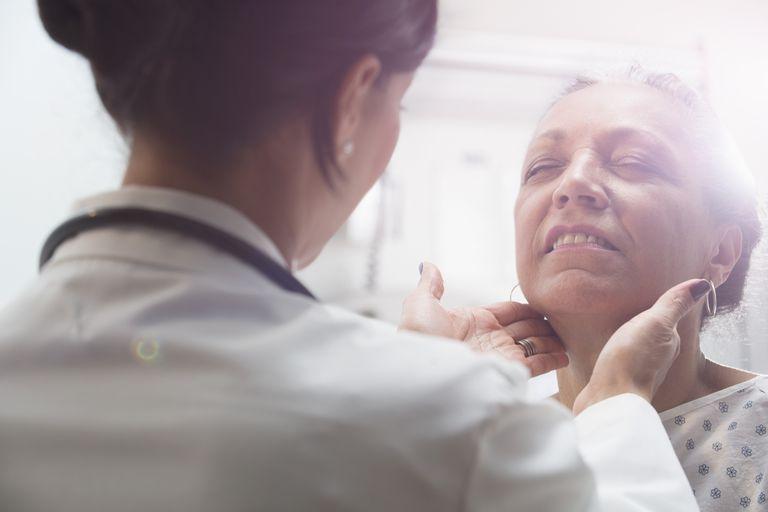 doctor examining female patient's neck