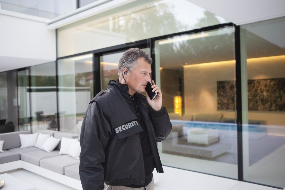 Mature security man using walkie-talkie in grounds of luxury home
