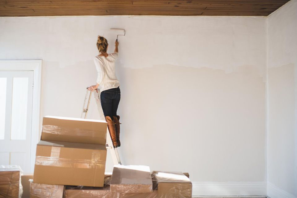Woman painting a new apartment with packed boxes