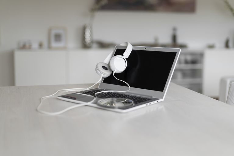 Laptop, headphones and CD on tabletop