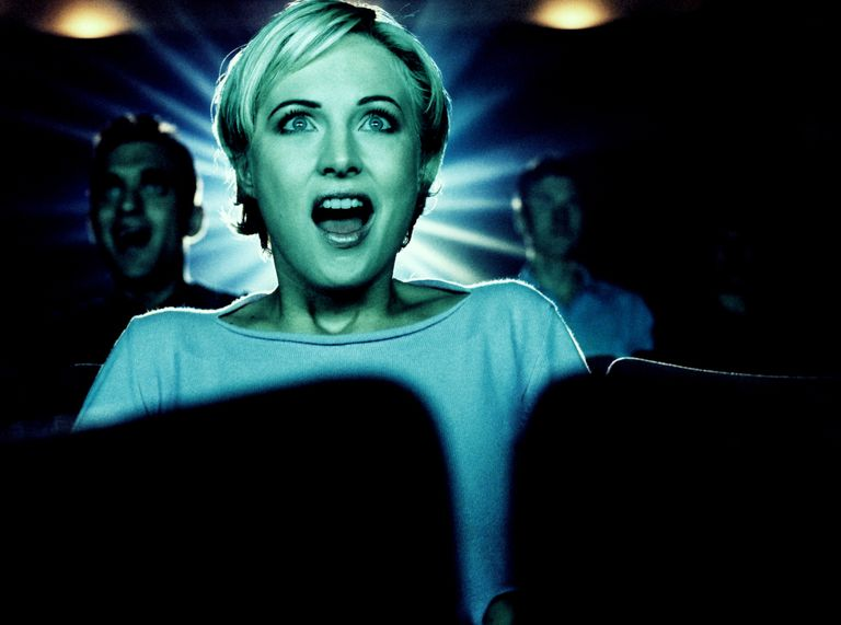 a woman in a movie theatre staring at the screen looking very excited.