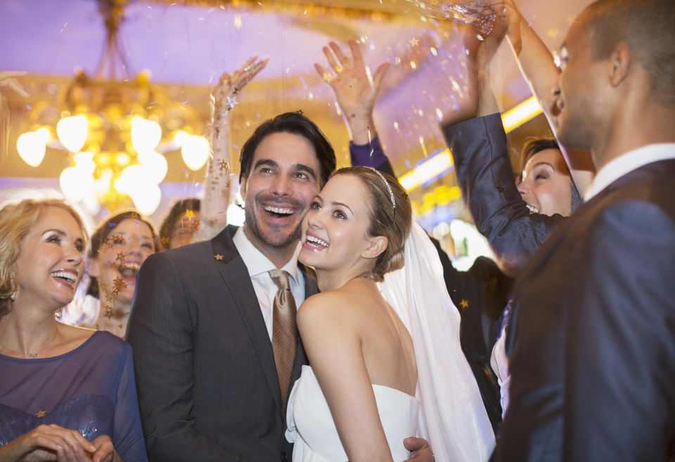 Friends throwing confetti over bride and groom at wedding reception