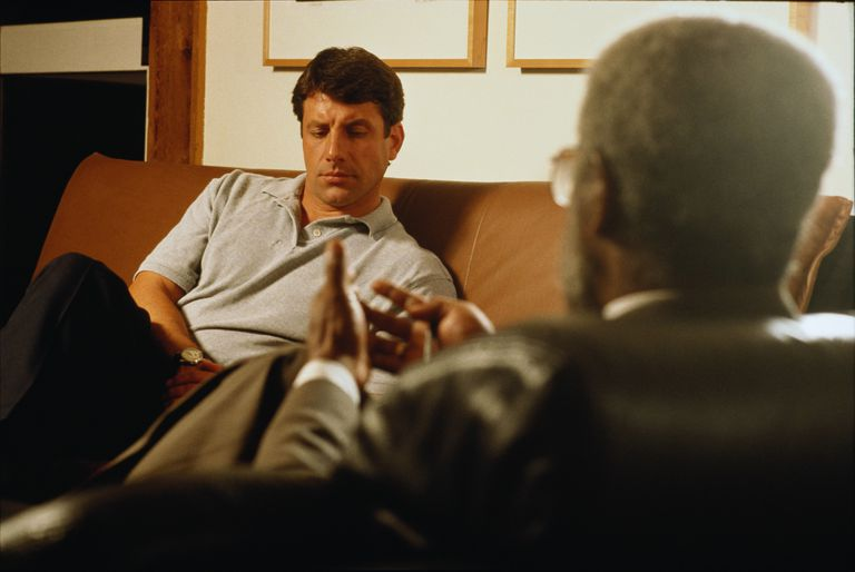 Man on sofa, looking pensive, listening to mature man in fore