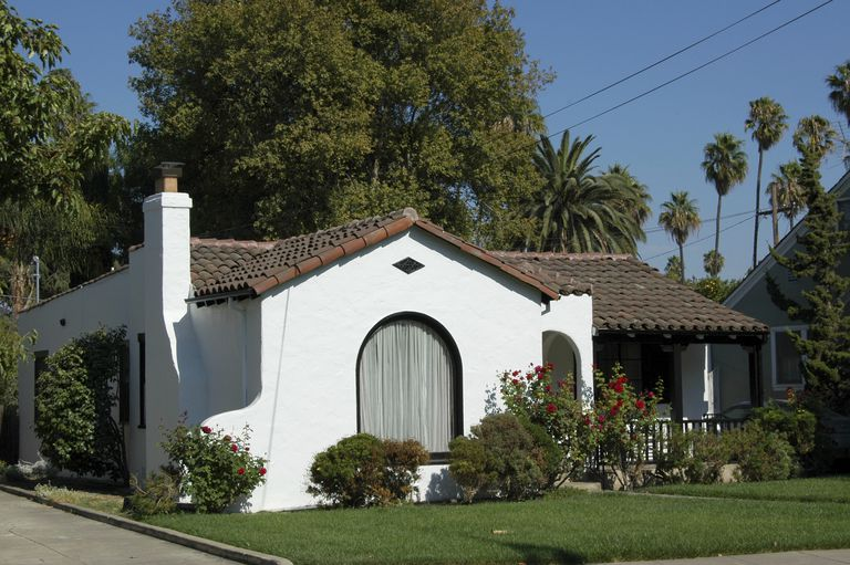 small white stucco home, one story, with brown tile roofing, large arched front window, and open porch half across the front