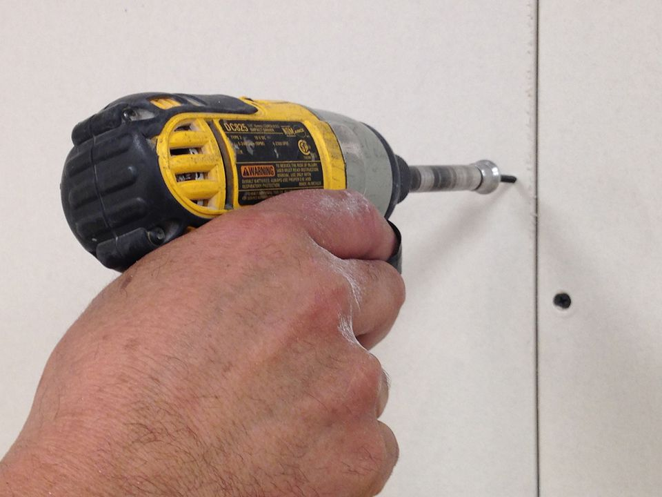 House remodeling - Installing Drywall using a drill.