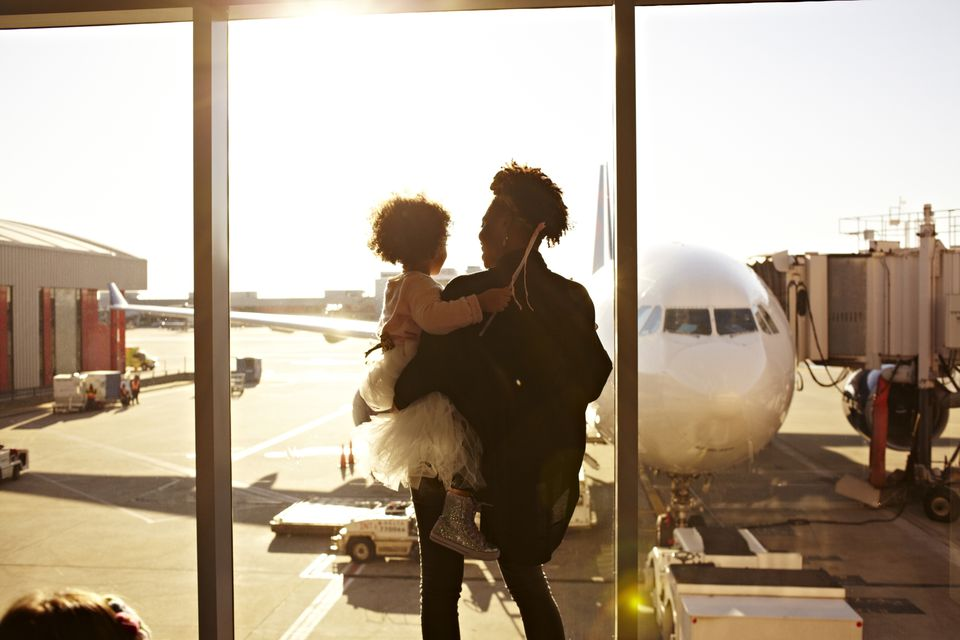 Mother holding daughter at airport