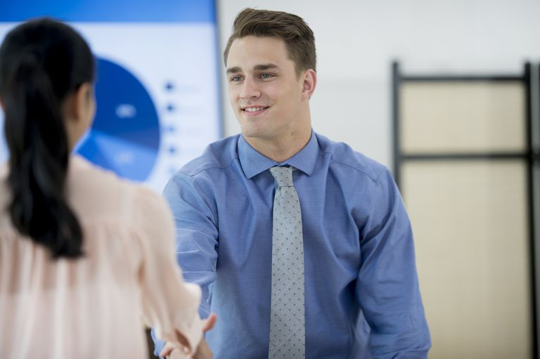 man shaking hands with woman in job interview