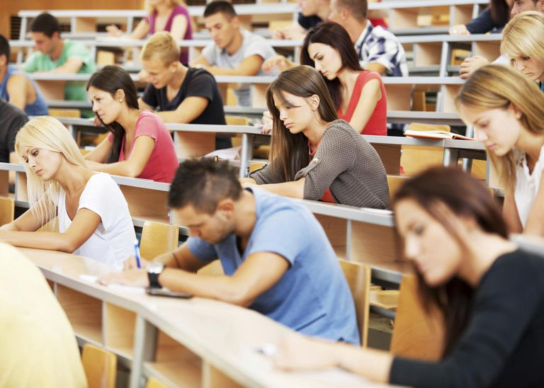 Large group of students writing. Group of ...