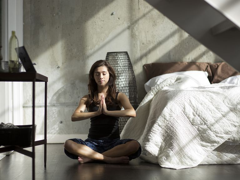 Woman practicing yoga on bedroom floor