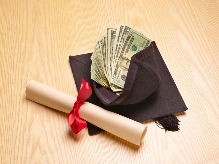 Rolled diploma and mortar board with US banknotes inside, studio shot