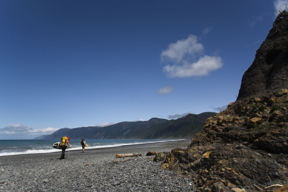 Two men hike with surfboards on The Lost Coast, California.