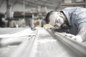 blue collar worker fabricating sheet metal