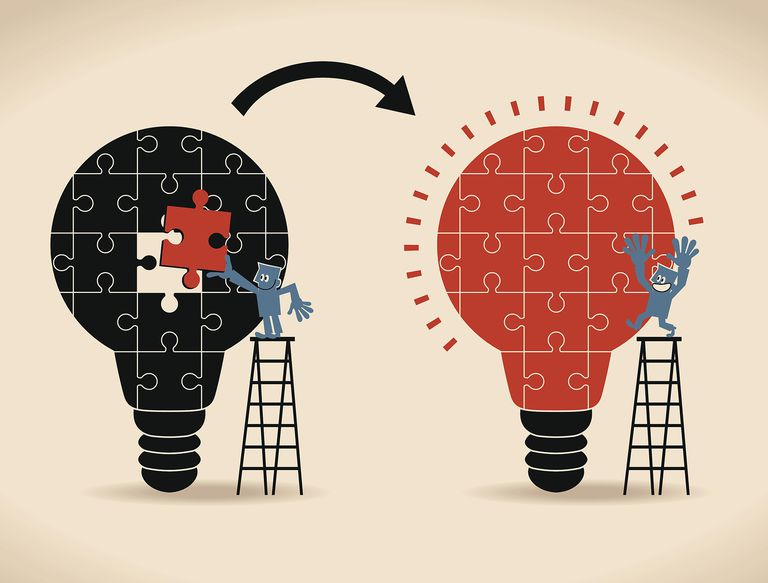 Businessman standing on ladder, completing an idea light bulb puzzle