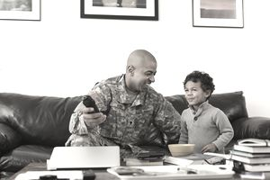 Mixed race soldier father and son watching television in living room
