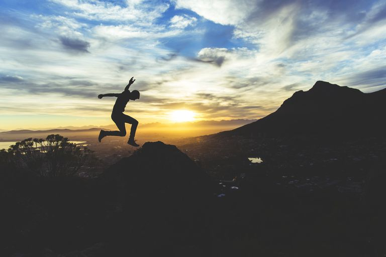 man jumping in the air at sunset