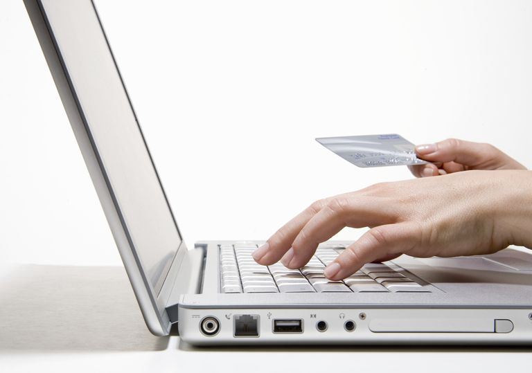 Woman holding bank card using laptop