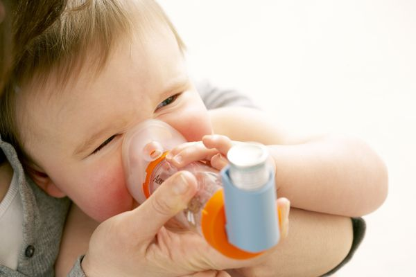 Baby with asthma using an inhaler.
