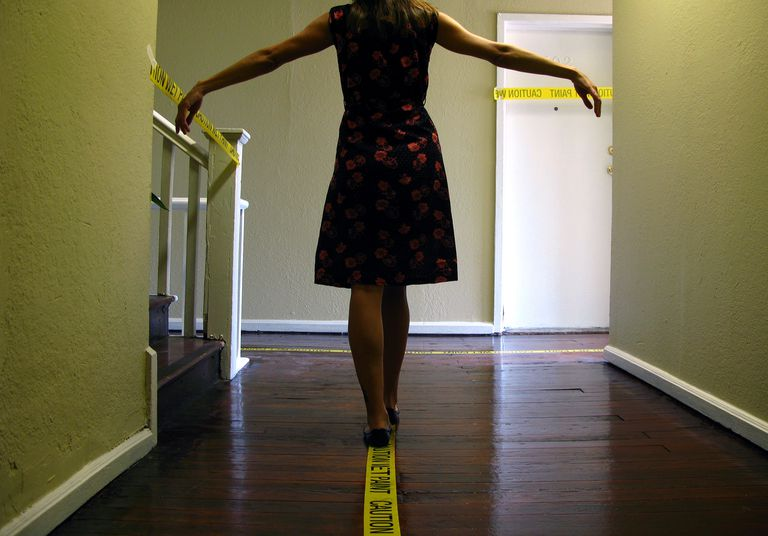 woman walking on caution tape inside home
