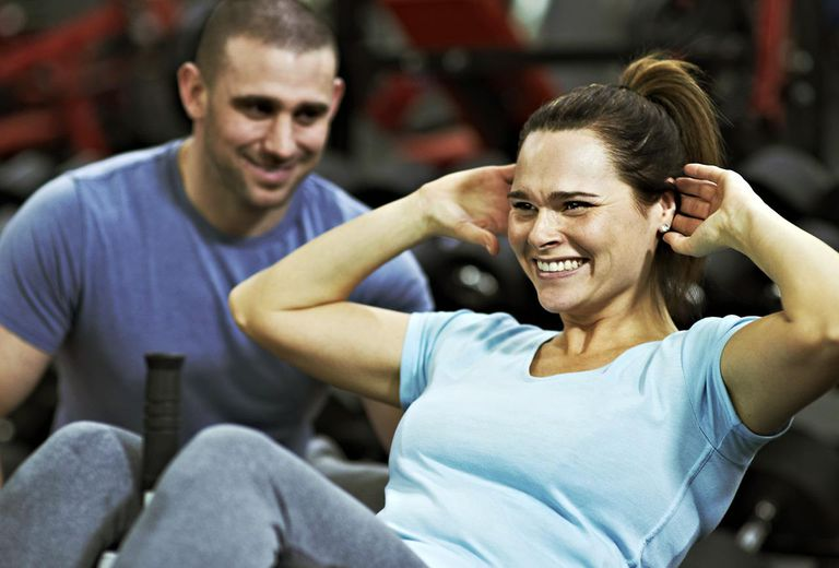 Active female doing sit ups in local gym, supported by personal trainer