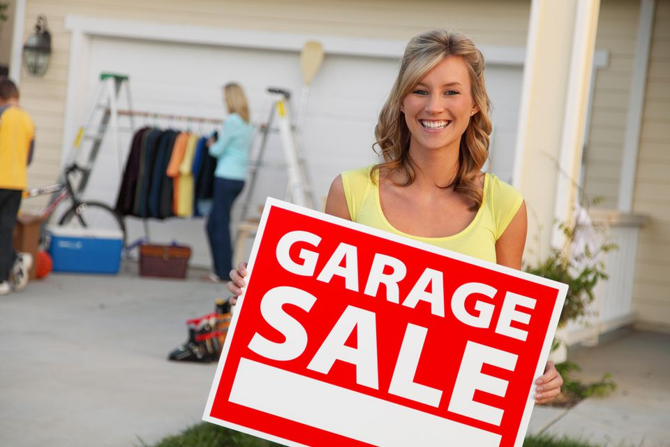 woman holding a garage sale sign
