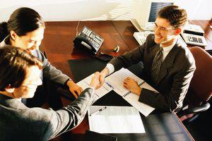 Woman and two men in meeting; men shaking hands over desktop
