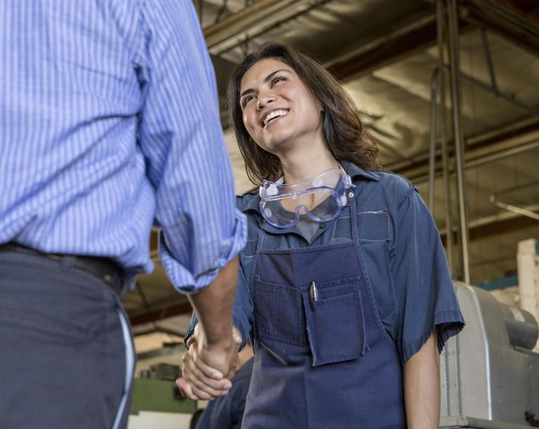 Warehouse supervisor greeting new female apprentice