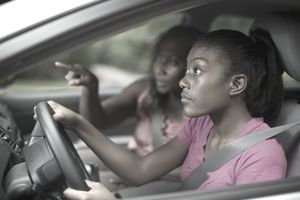 African American teen learning to drive with mom