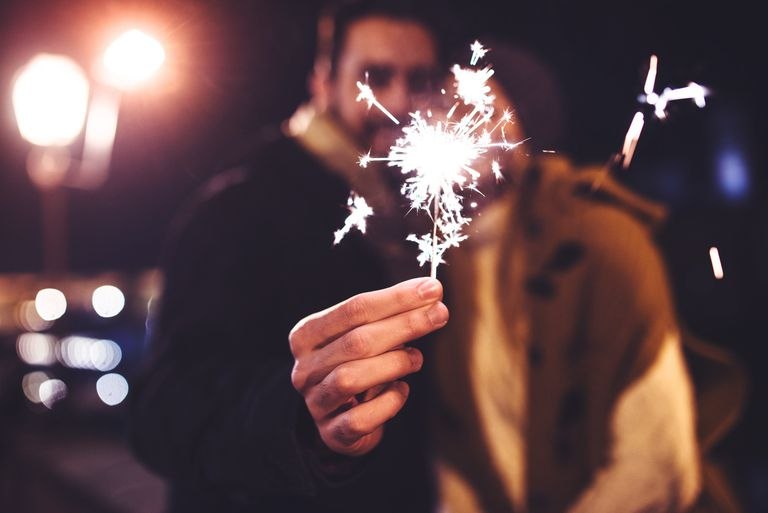 Couple holding sparkler to celebrate the new year
