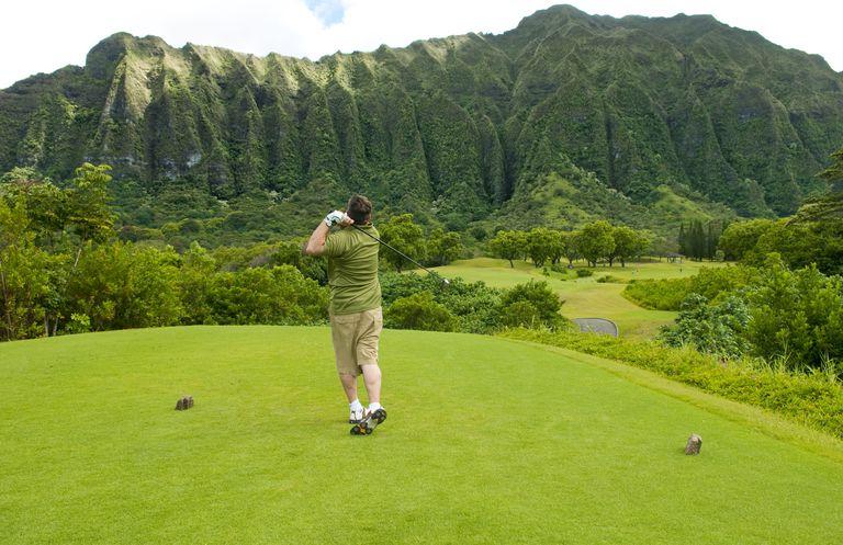 Hawaii, Oahu, Honolulu, Ko'olau Golf Course, Man driving on the 5th hole with beautiful mountain view.