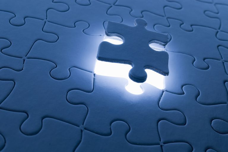 Photo of a puzzle piece floating above a puzzle