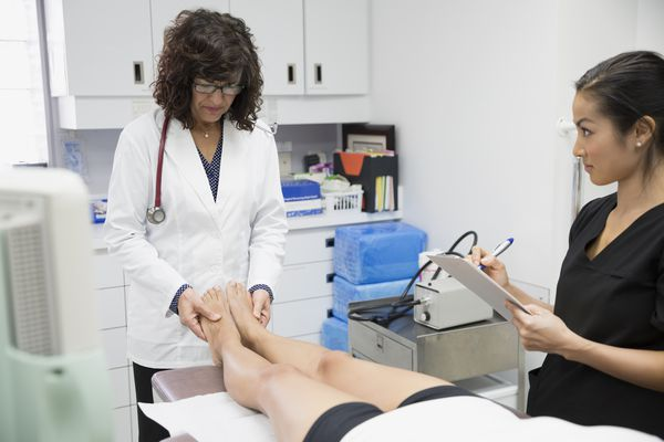 Doctor examining womans legs in examination room