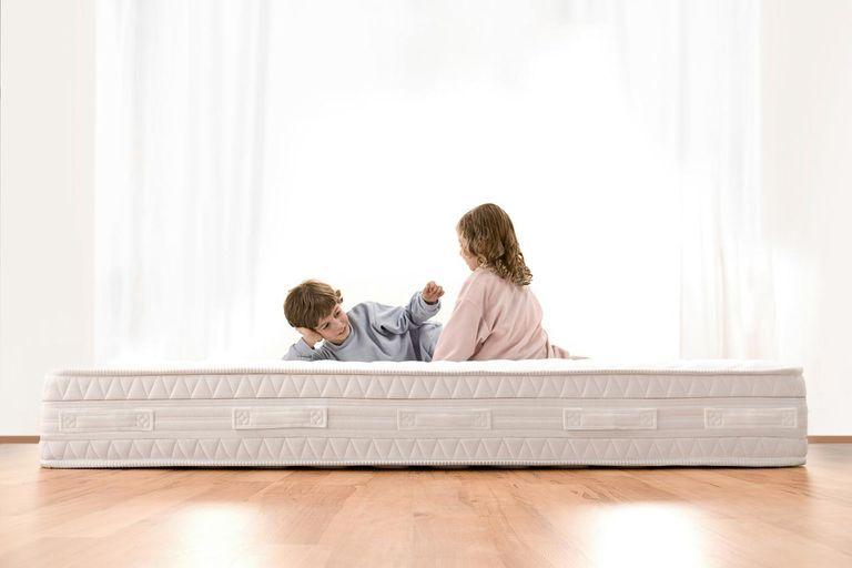 Two kids playing on mattress