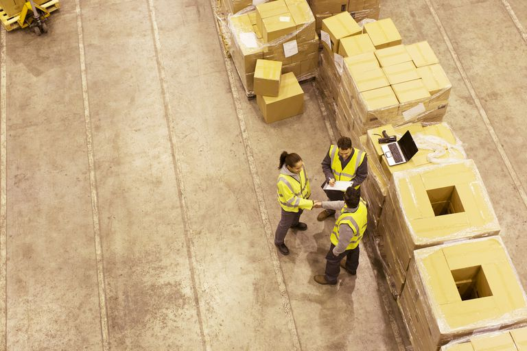 workers standing next to freight in boxes