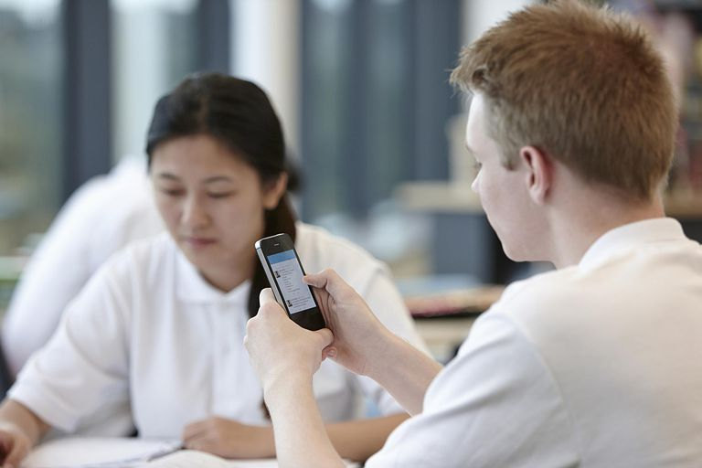 Teenage boy using cell phone in classroom