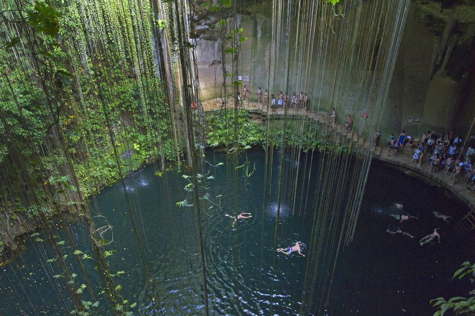 Tourists swimming in Ikil cenote on Yukatan peninsula in Mexico